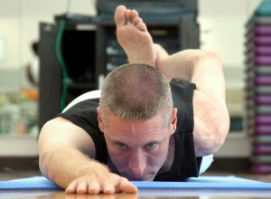 A military person stretches in a yoga pose